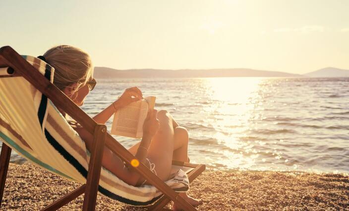 Frau am Meer im Last-Minute-Urlaub