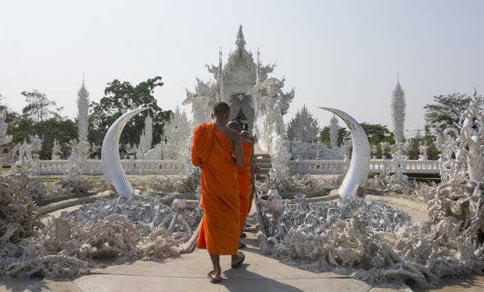 Mönch vor Wat Rong Khun Tempel in Thailand