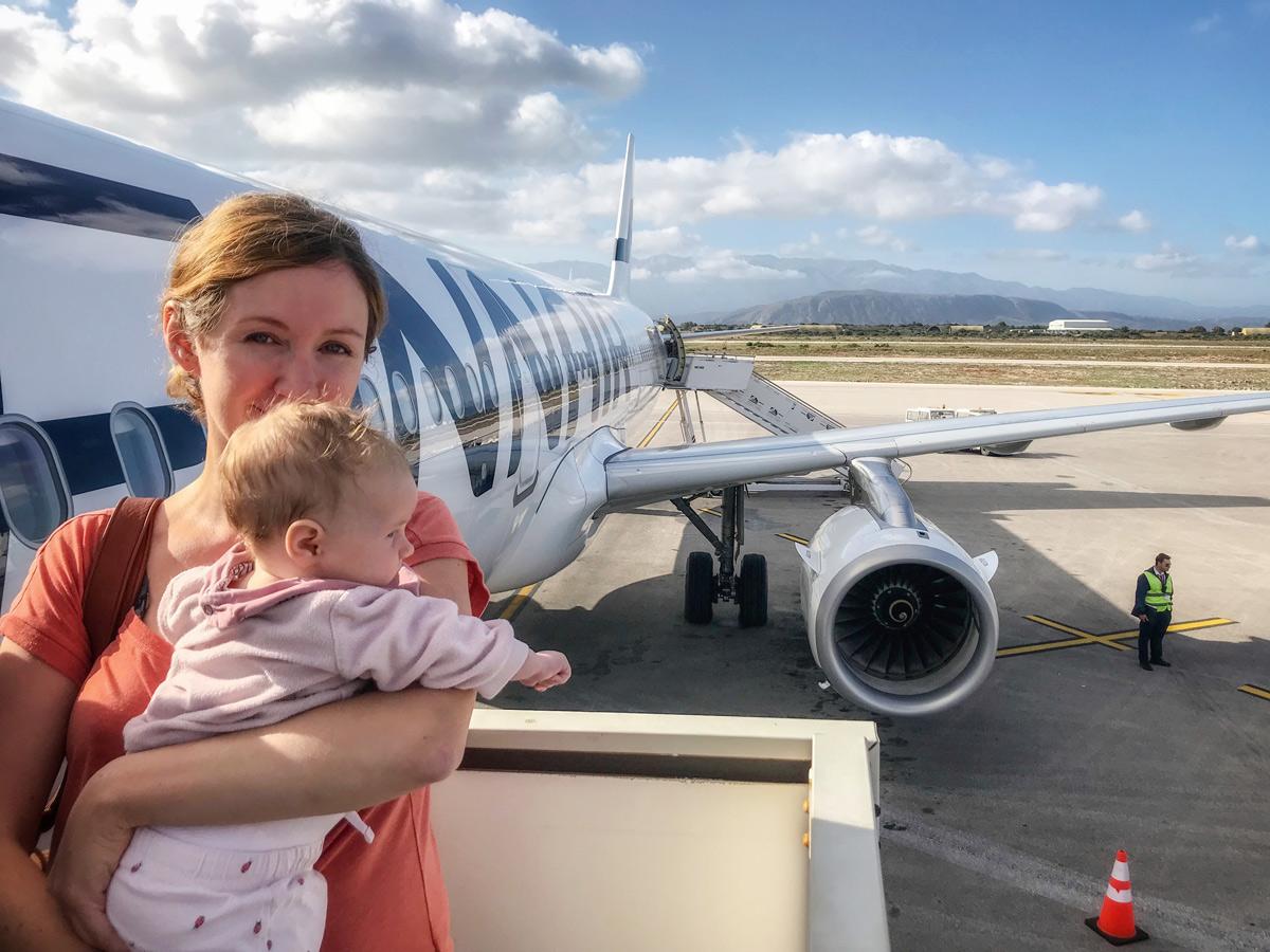 Frau mit Baby vor Flugzeug