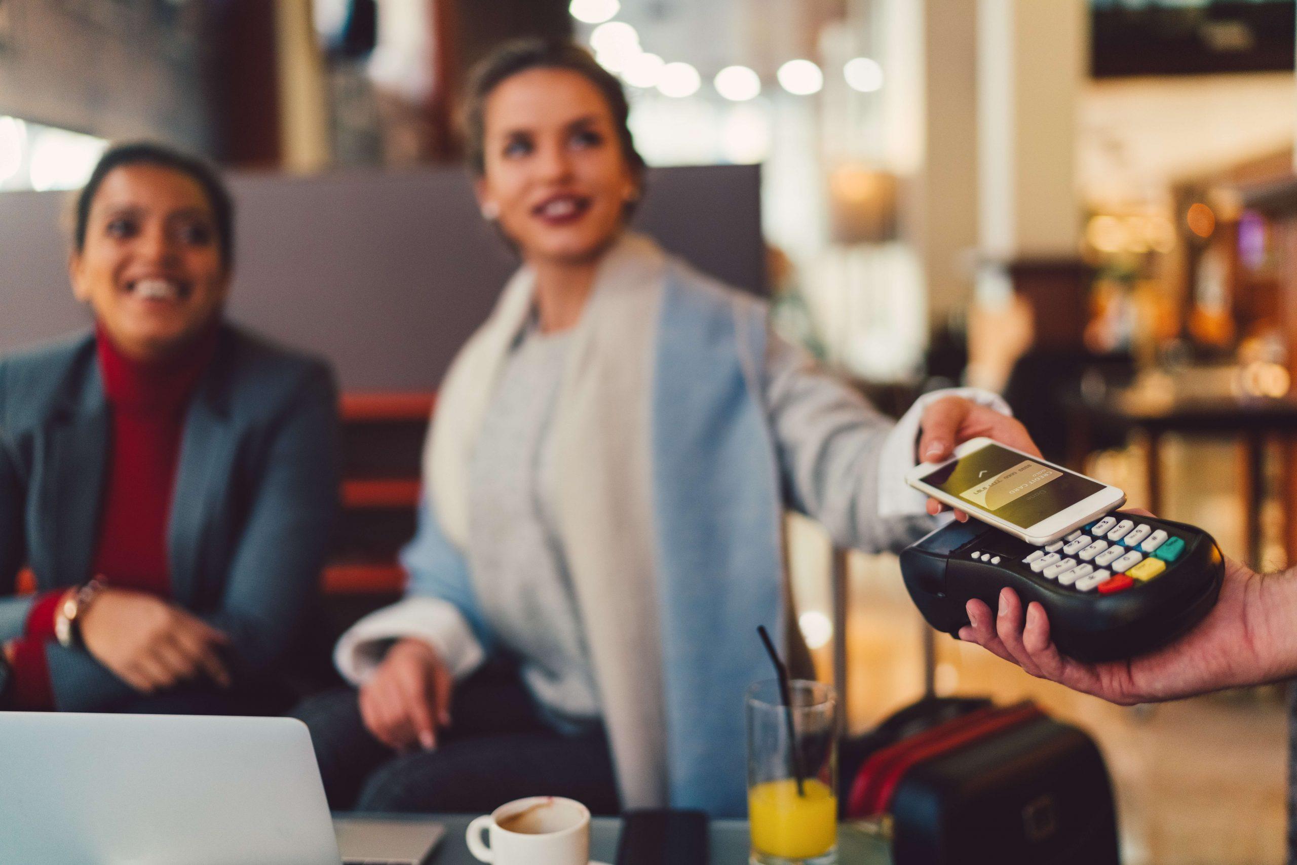 zwei Frauen im Cafe bezahlen mobil mit Smartphone