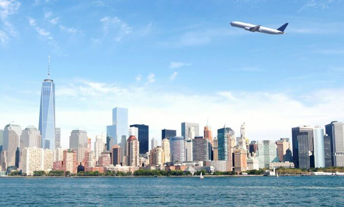 Amazing view of New York City featuring an airplane, The One World Trade Center and skyline.