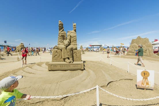 British Columbia, Canada - July 14, 2015: Tourists and locals come to see the winning sand sculpture of Batmand and Joker at the annual sand sculpture competition in Parksville, Vancouver Island