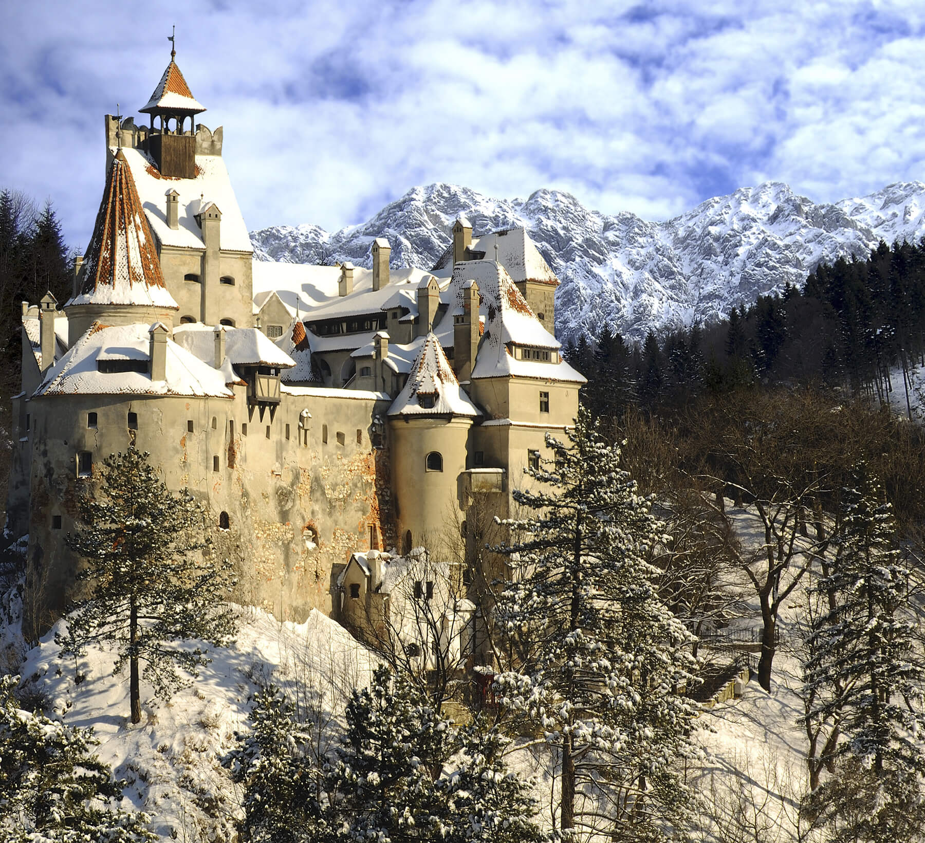 Bran, Romania - March 01, 2009 : Dracula's Bran Castle in winter with snow and Piatra Craiului (Carpathians) mountains.