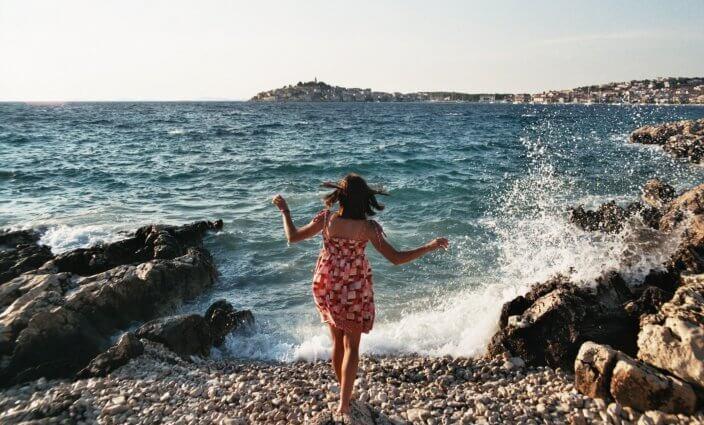 junge Frau im Last-Minute-Urlaub am Wasser